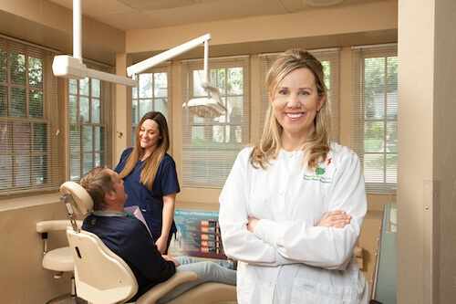 Dr. Jacqueline Bennett stands in a dental exam room with a dental patient and hygienist in the background